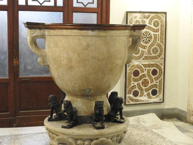 Døbefont - eller døbeamfora - fra græsk tid. Løverne under fonten er ligesom mosaikkerne i baggrunden fra den normanniske periode. Foto: KirstenSoele